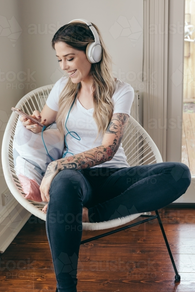 20 something girl listening to a podcast with headphones - Australian Stock Image