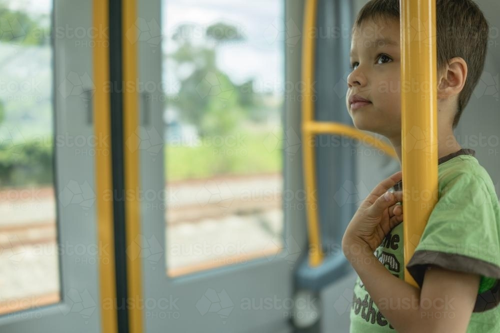 6 year old mixed race boy rides on a Sydney city train - Australian Stock Image