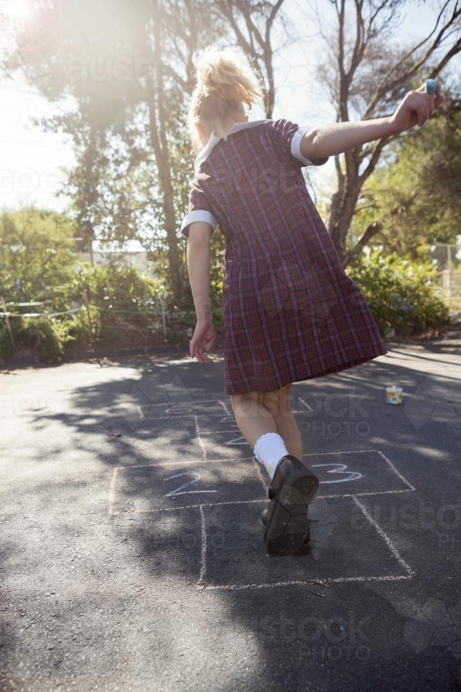 7 year old girl playing hopscotch in school uniform on asphalt - Australian Stock Image