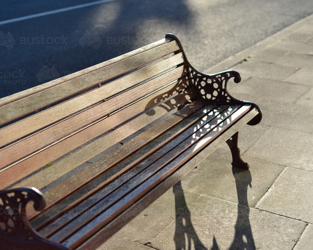 A classic wooden public bench in the afternoon sun - Australian Stock Image