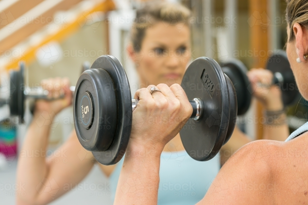 A fit woman lifting weights in front of a gym mirror - Australian Stock Image