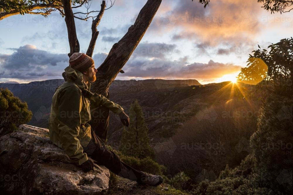 A hiker watching the sunset beside the Overland Track - Australian Stock Image