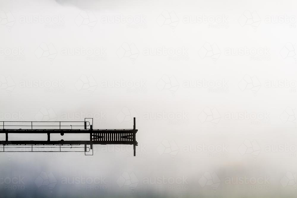 A jetty floats into the middle of a misty Huon River - Australian Stock Image