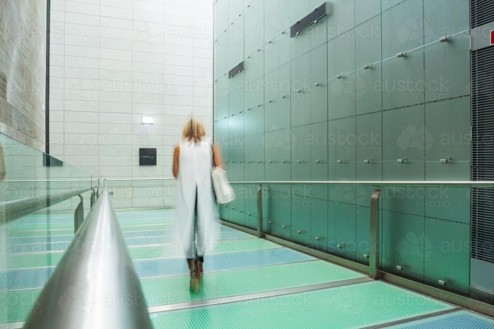 A lady walking through a gallery corridor - Australian Stock Image