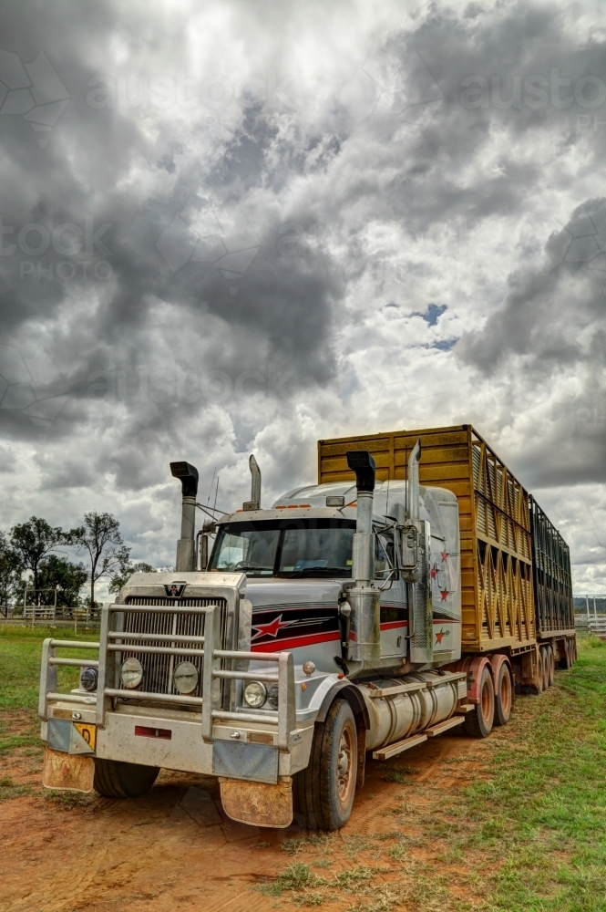 A livestock B-Double semi-trailer truck under a stormy rural sky - Australian Stock Image