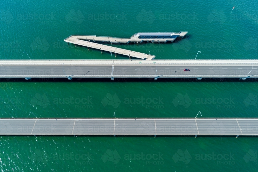 A lone car driving over a bridge above water. - Australian Stock Image
