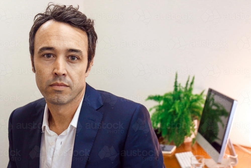 A male office worker standing in front of work desk - Australian Stock Image