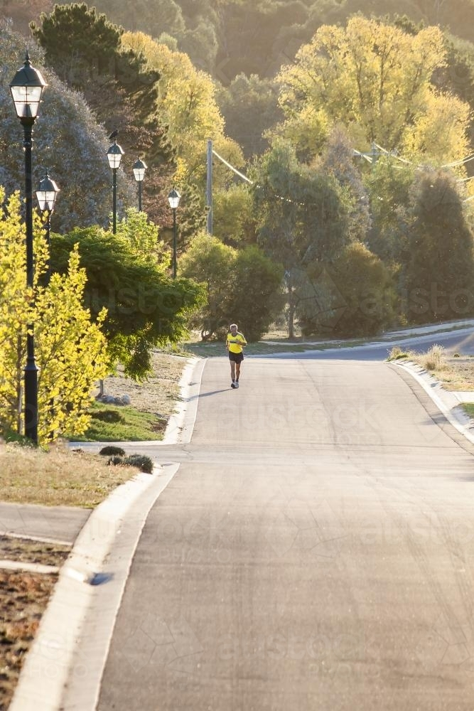 A man running up a residential street - Australian Stock Image