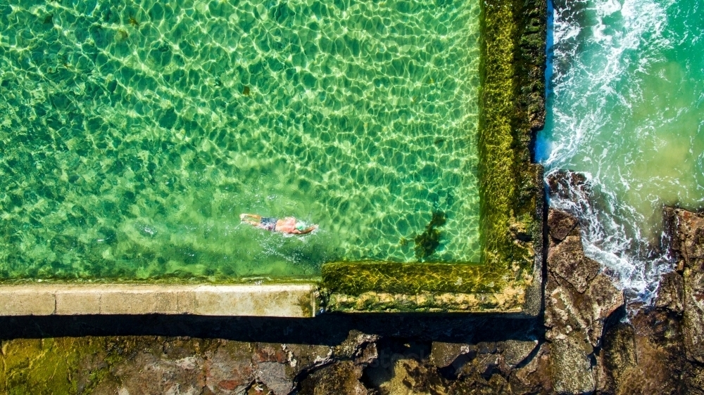 A mature man swimming laps in the Austinmer Rock Pool as waves lap the edges - Australian Stock Image
