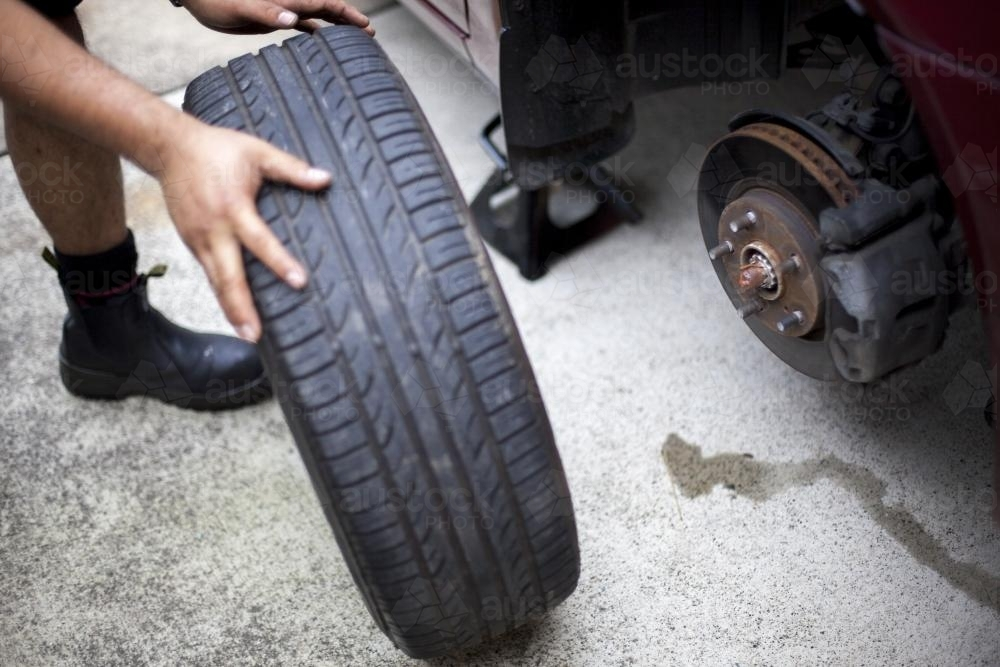 A mechanic inspects a tyre during a vehicle service. - Australian Stock Image