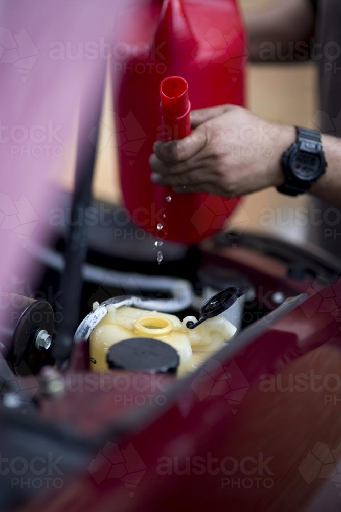 A mechanic refills windscreen washer fluid. - Australian Stock Image