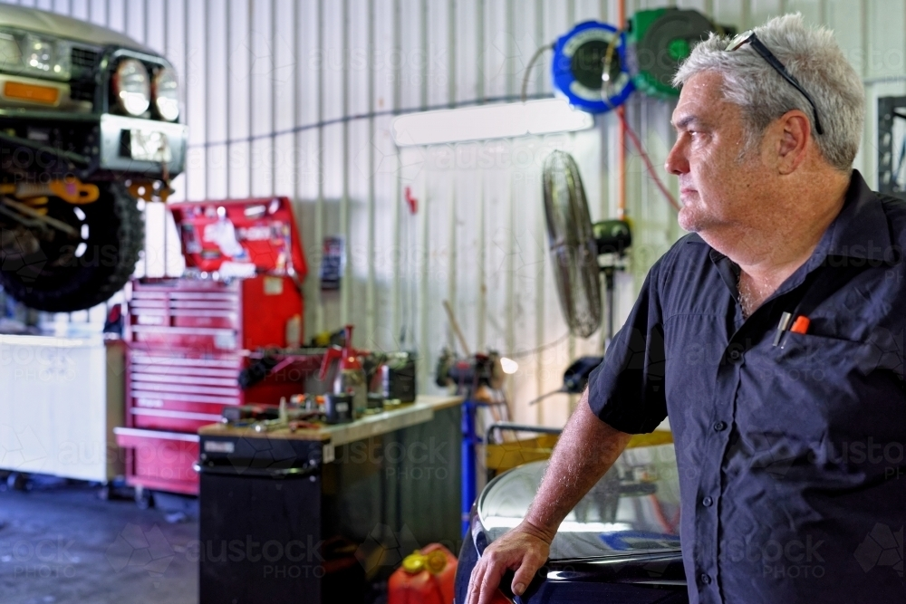 A mechanic standing in his workshop on the Gold Coast looking out - Australian Stock Image