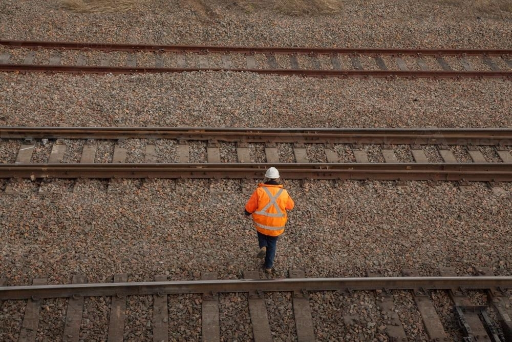 A person walking over three train tracks from overhead - Australian Stock Image