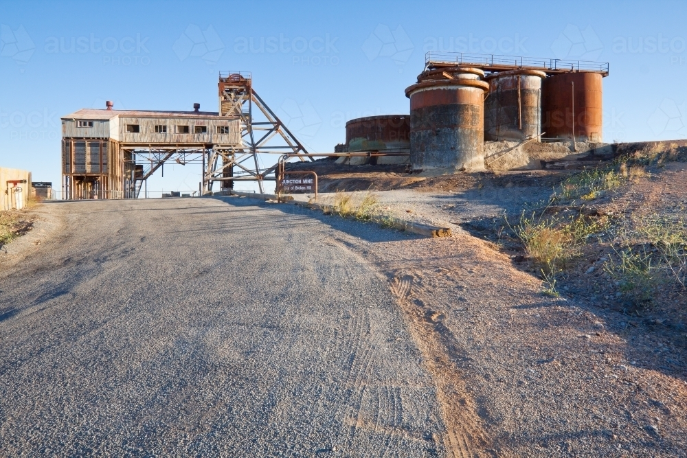 A road leading up to rusted tanks and abandoned buildings of an closed mine - Australian Stock Image