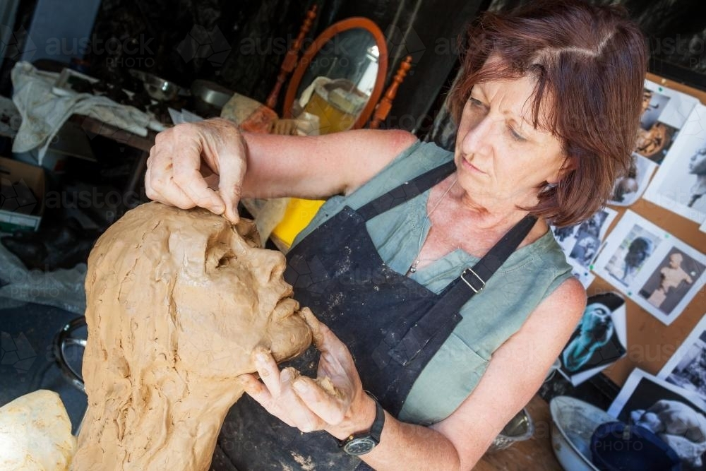 A sculptor working on a clay bust - Australian Stock Image
