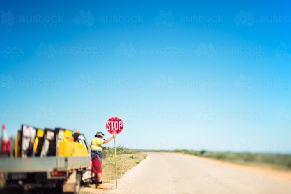 A solitary road worker holds a stop sign on a deserted road in the middle of nowhere - Australian Stock Image