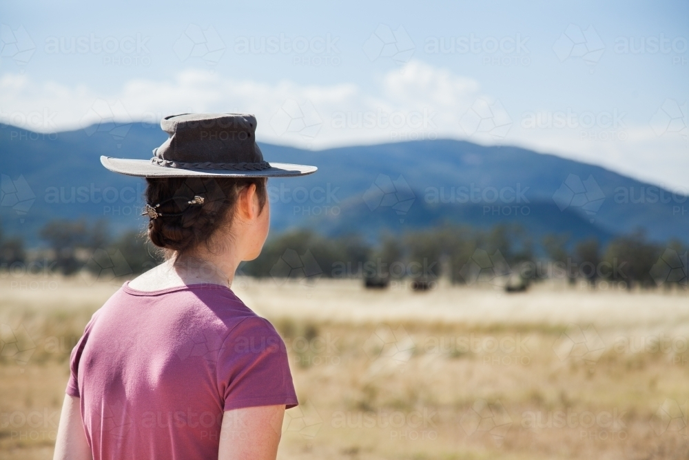 d585860f985 A teen farm kid in an akubra hat standing in farm paddock - Australian  Stock Image