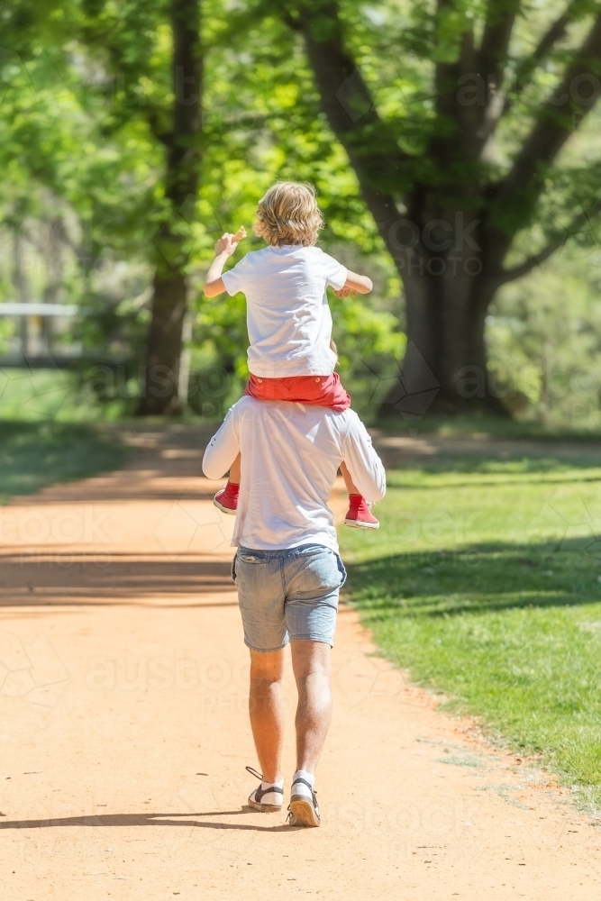 A teenager walking in a park with his little brother on his shoulders - Australian Stock Image