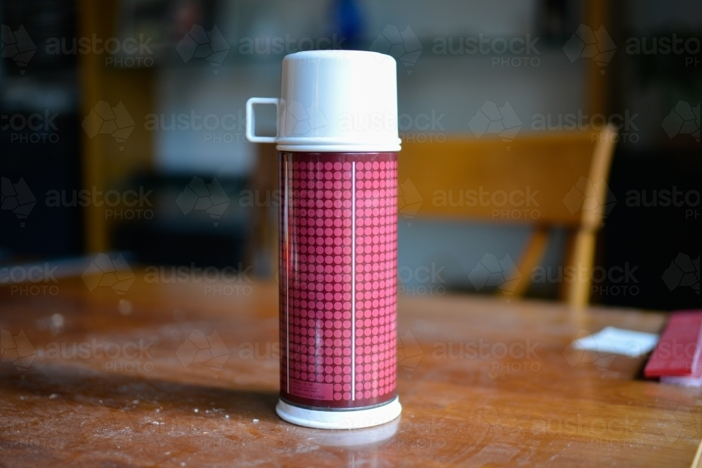 A thermos flask sits on a table during a renovation - Australian Stock Image
