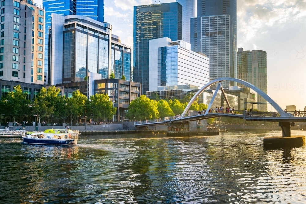 A tourist boat on inner city river with high rise buildings along its banks - Australian Stock Image