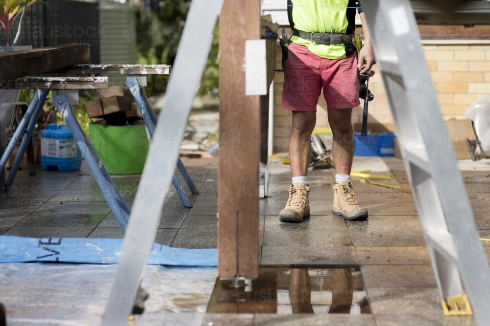 A tradesman standing outside on a home renovation site. - Australian Stock Image