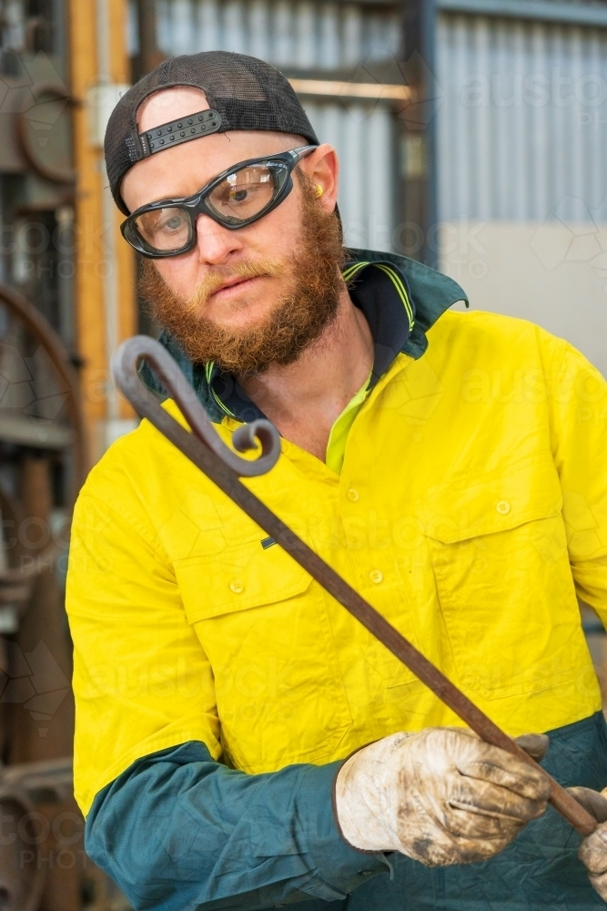 A tradesman wearing high vis clothing examining the bends in a curved steel rod - Australian Stock Image