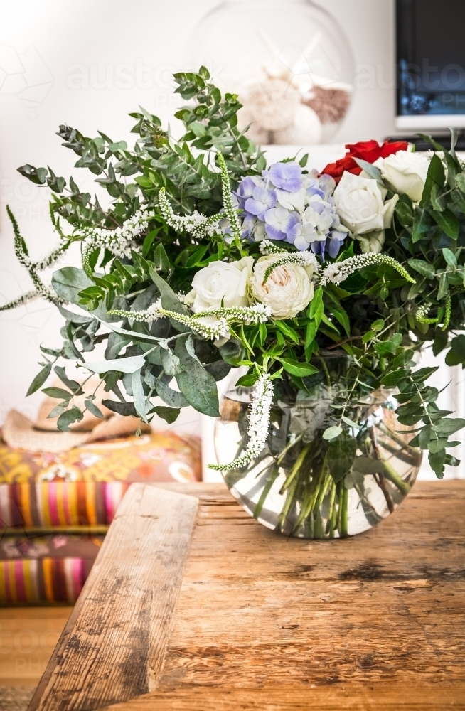 A vase of flowers on the coffee table in a country home - Australian Stock Image