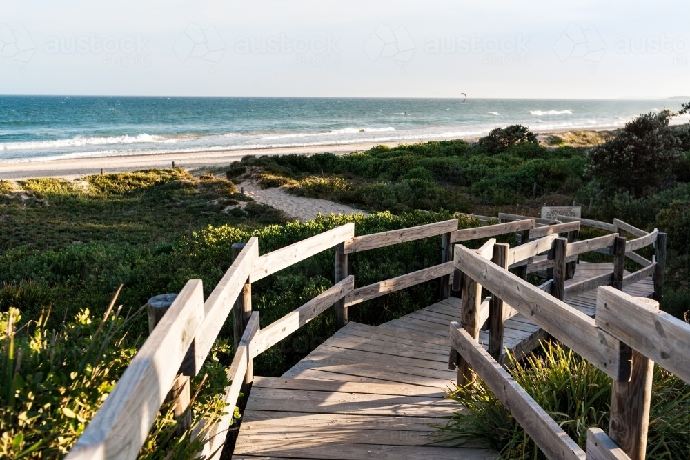 A winding, wooden boardwalk platform providing access to the beach and beach plants - Australian Stock Image