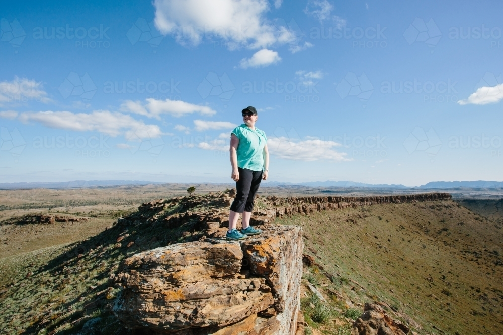 A woman in hiking gear overlooking the rugged landscape of the Flinders Ranges - Australian Stock Image