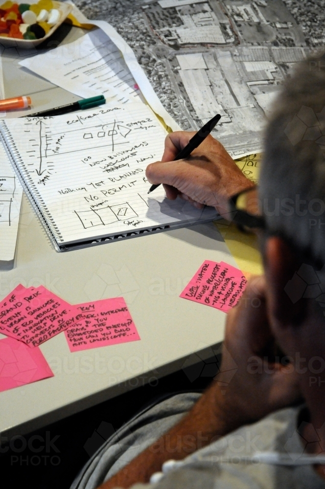 A workshop participant putting his ideas on paper - Australian Stock Image
