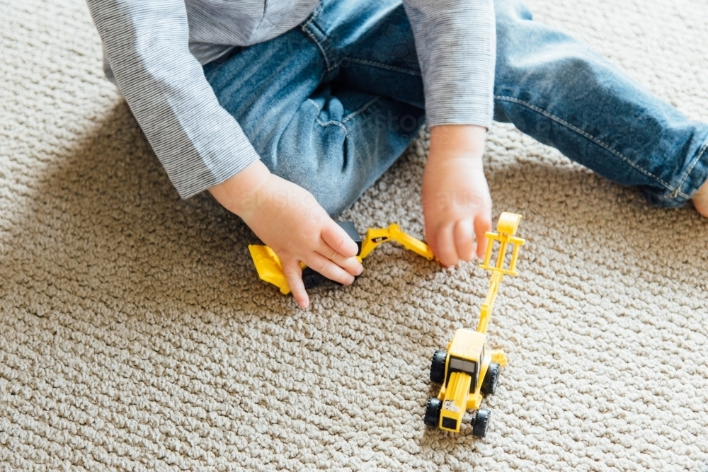 A young boy playing with a small yellow toy digger - Australian Stock Image