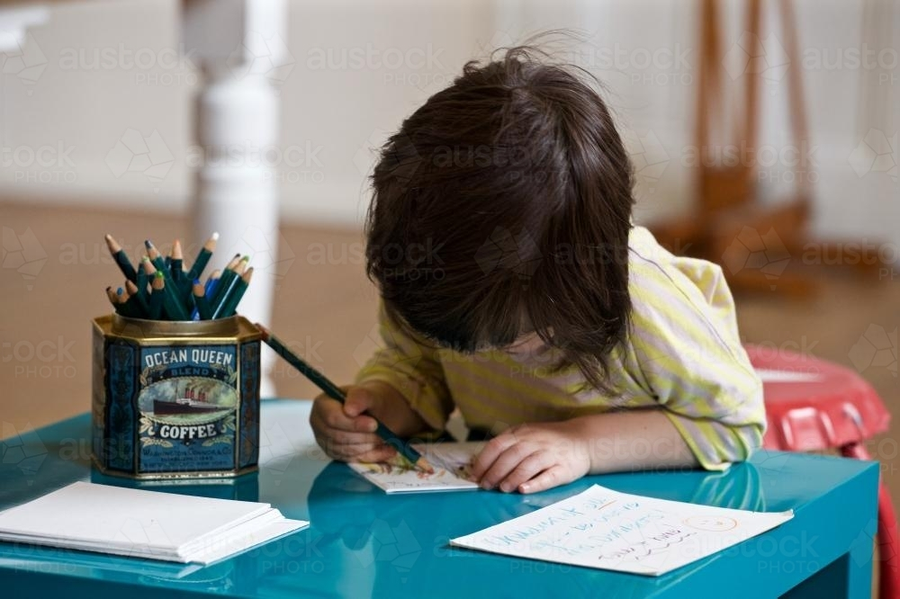 A young girl / child sits at a desk drawing with pencils