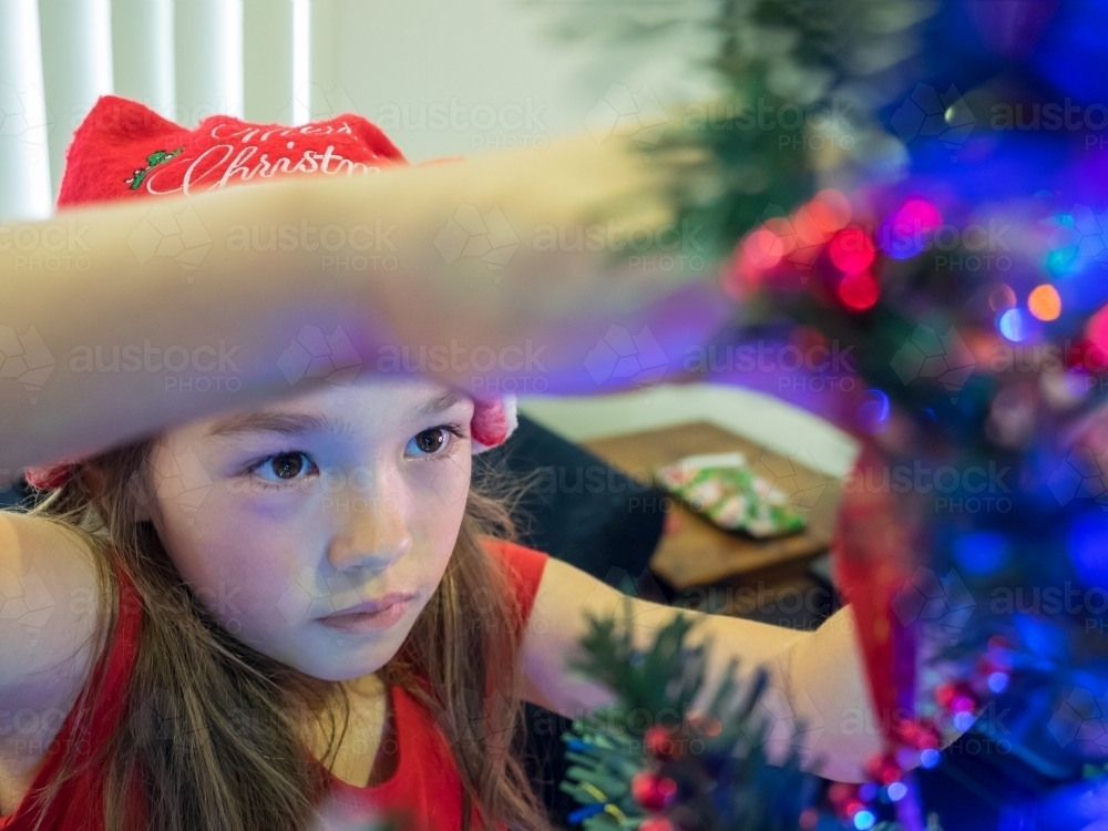 A young girl of mixed race decorating a Christmas tree - Australian Stock Image
