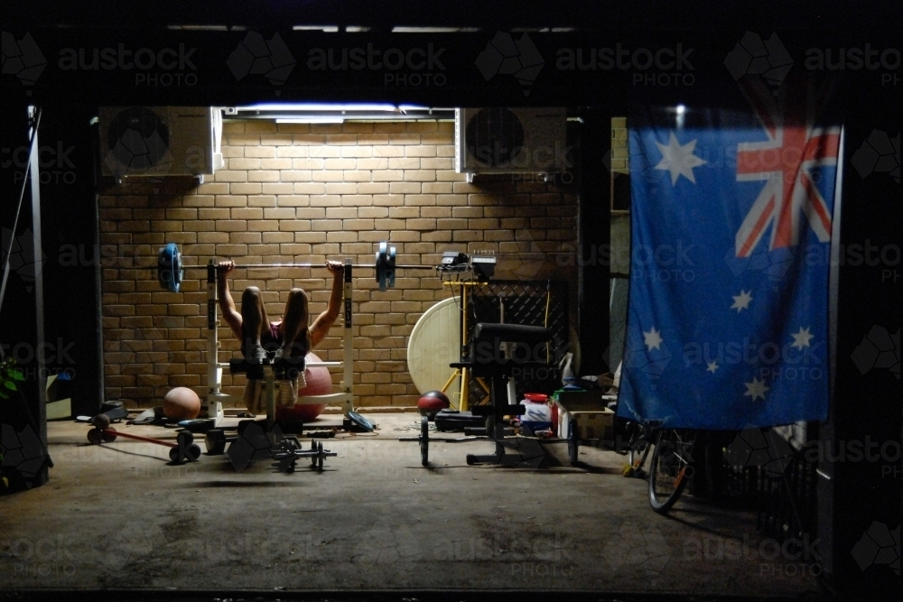 A young man doing weights at night near an Australian flag - Australian Stock Image