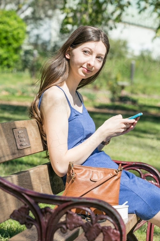 A young woman with long hair sitting on a park bench with her phone in her hands - Australian Stock Image