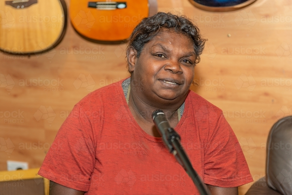 Aboriginal lady singing and playing music - Australian Stock Image