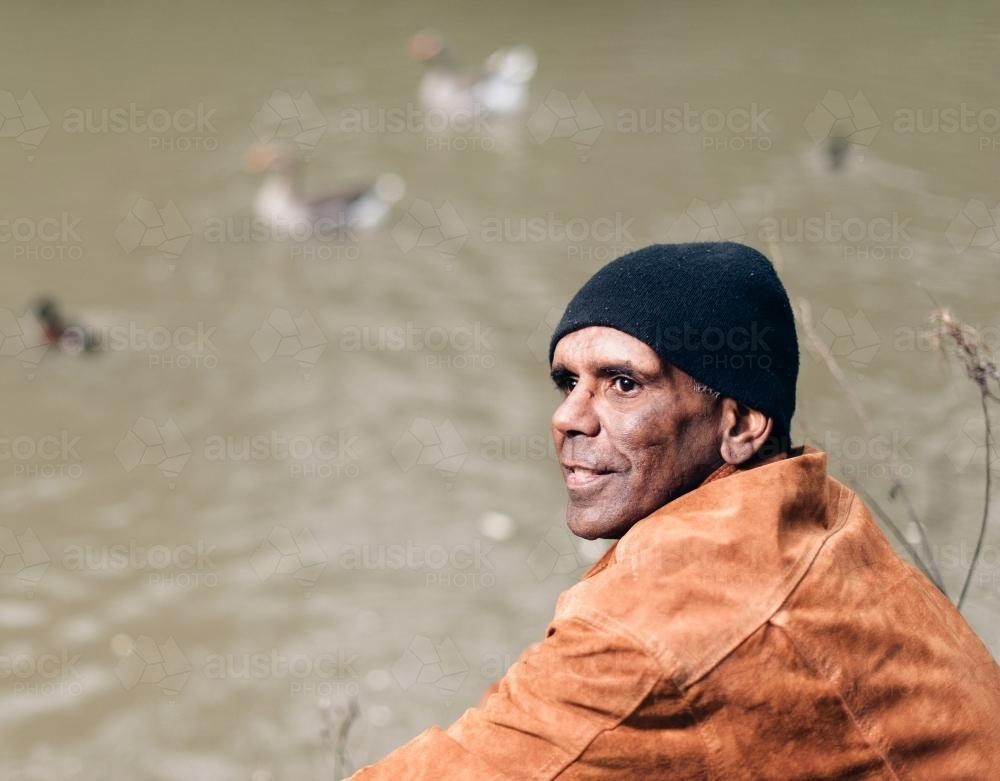 Aboriginal Man in his Forties, River in Background - Australian Stock Image