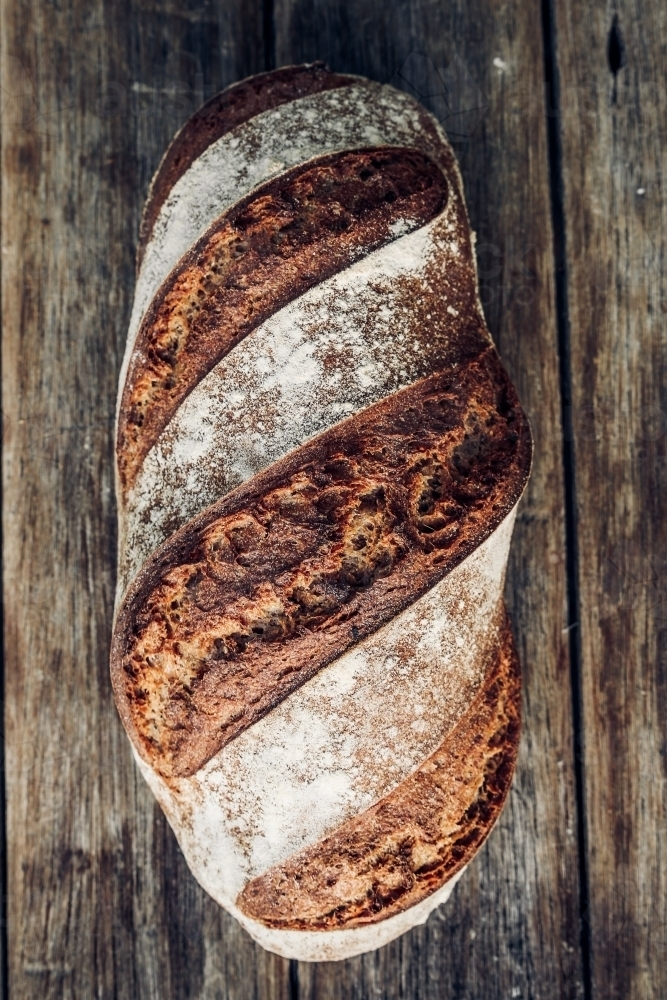 Above shot of a fresh baked loaf of spelt sourdough bread on a wooden bench - Australian Stock Image
