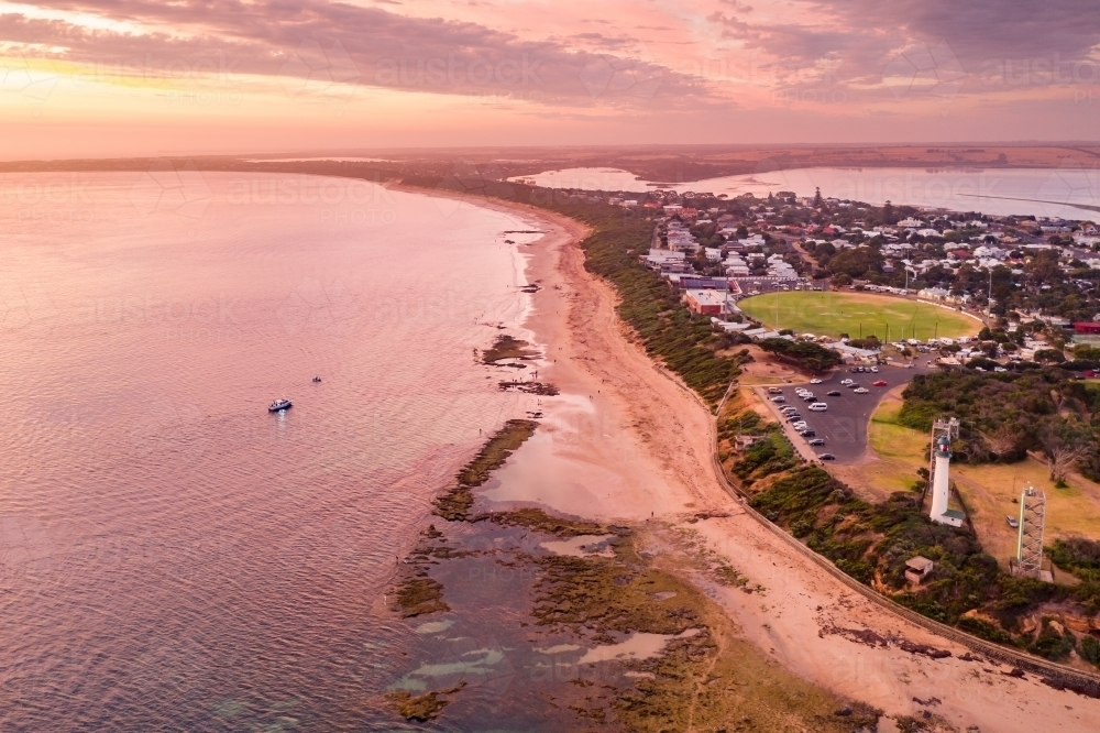 Aerial view of a coastal town and lighthouse at sunset - Australian Stock Image
