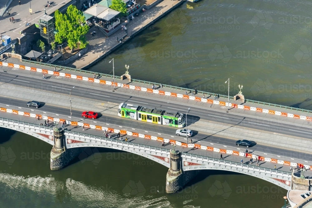 Aerial view of a commuter tram going over an historic arched bridge - Australian Stock Image
