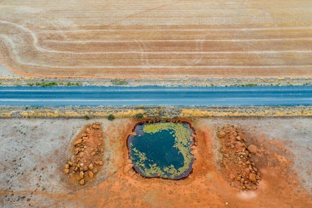 Aerial view of a country road next to a dam on dried farmland. - Australian Stock Image