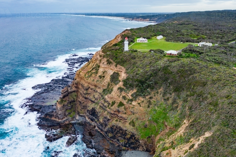 Aerial view of a lighthouse perched on a clifftop above a rugged coastline - Australian Stock Image