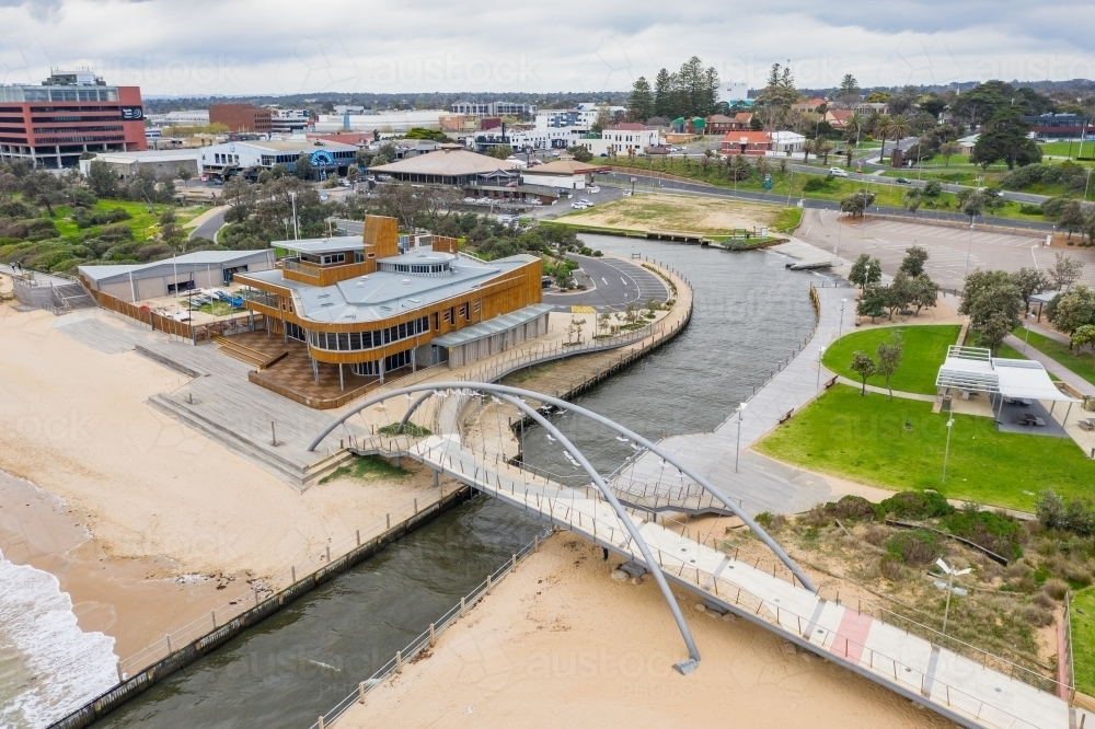 Aerial view of a modern arched walking bridge over a marina channel flowing out to sea. - Australian Stock Image