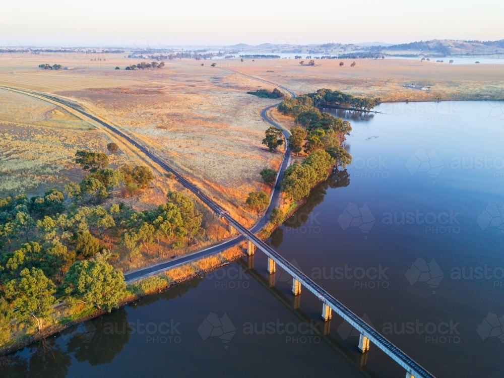Aerial view of a railway bridge crossing a lake in early morning sunshine - Australian Stock Image