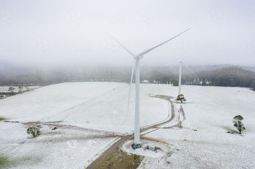 Aerial view of wind turbines in a foggy sky on a snow covered hilltop - Australian Stock Image