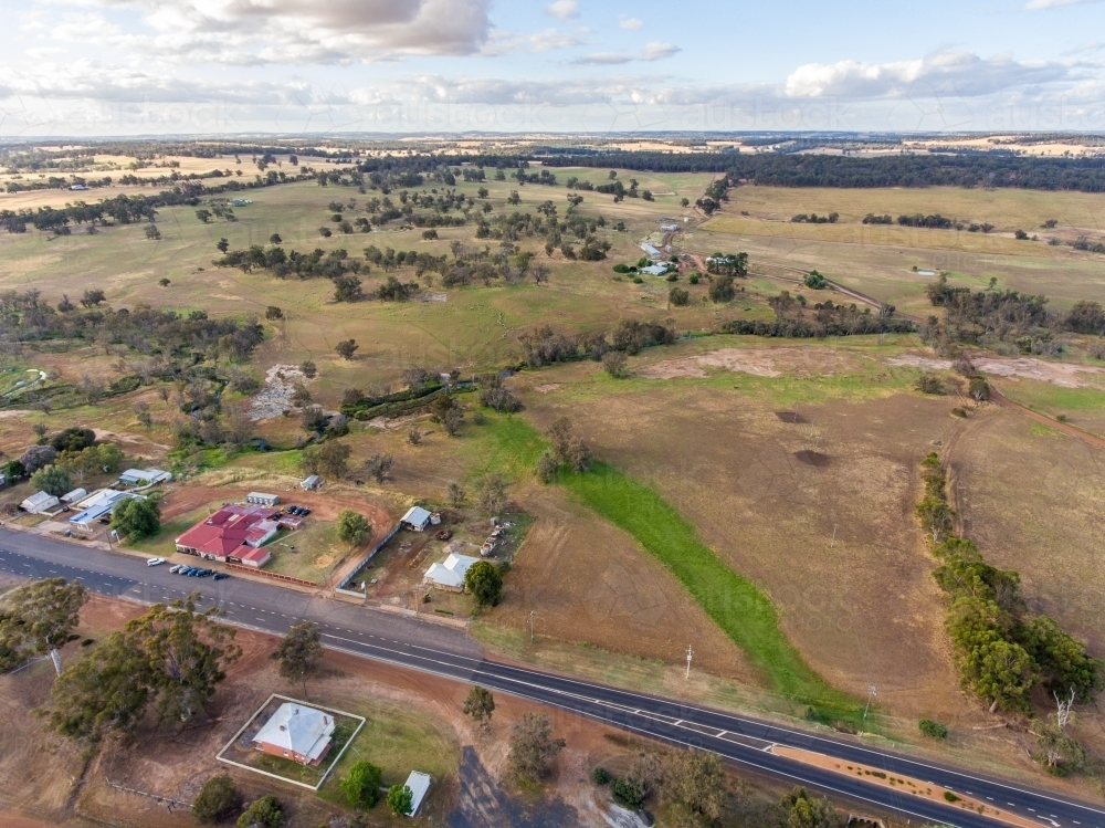 aerial view over outskirts of small town with farmland to the horizon - Australian Stock Image