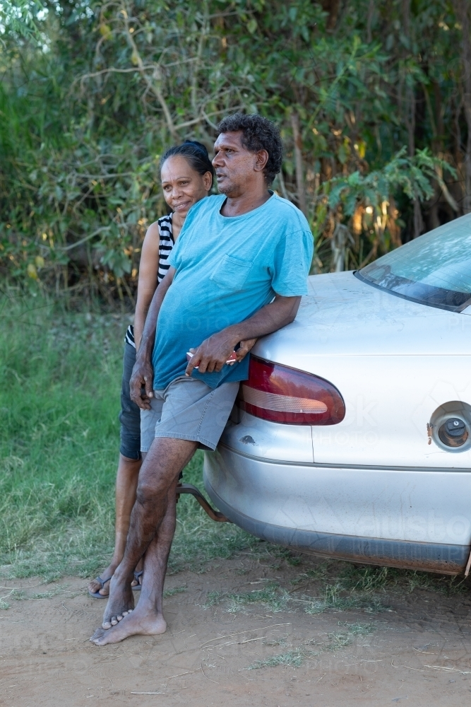 affectionate mature couple leaning on the boot of their car - Australian Stock Image