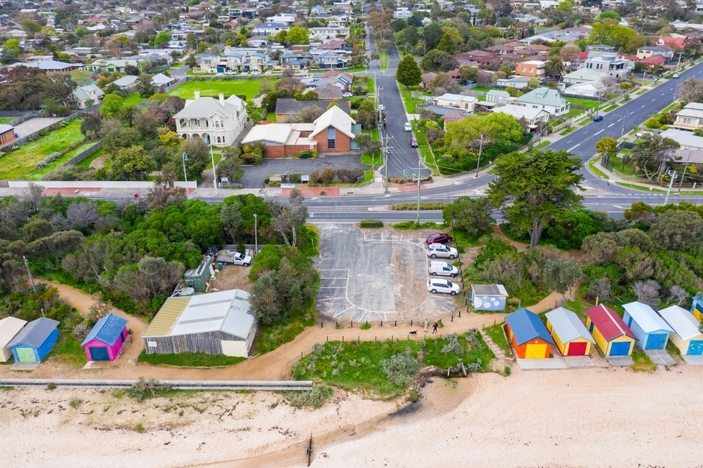 An aerial view of a small coastal car park between rows of brightly colored bathing boxes - Australian Stock Image