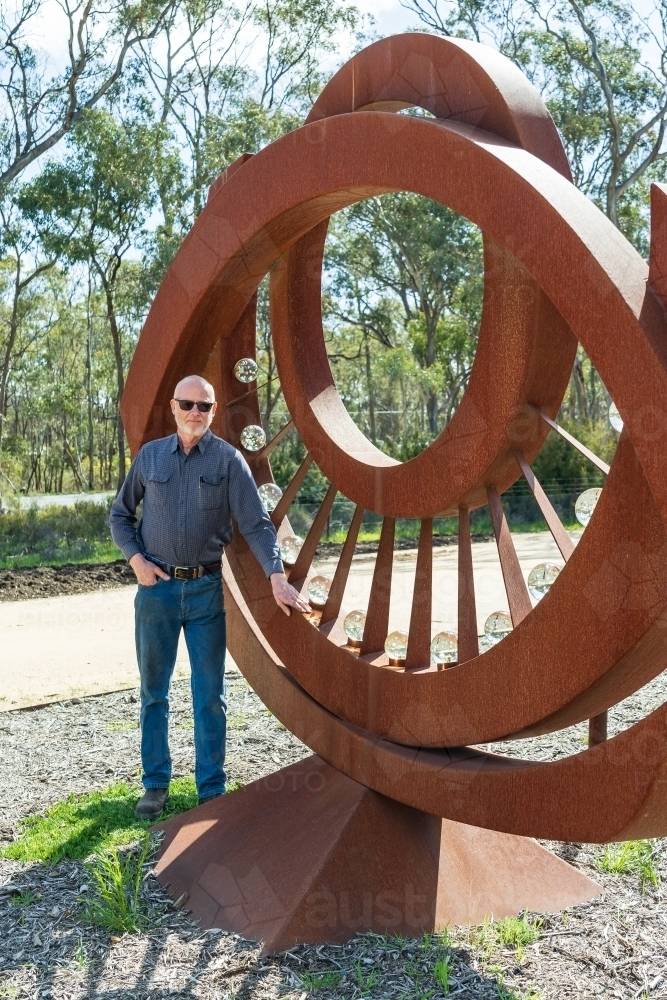 An artist standing proudly in front of a large metal sculpture - Australian Stock Image