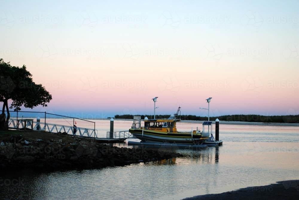 An Australian Volunteer Coast Guard boat is moored in Caloundra at sunset - Australian Stock Image